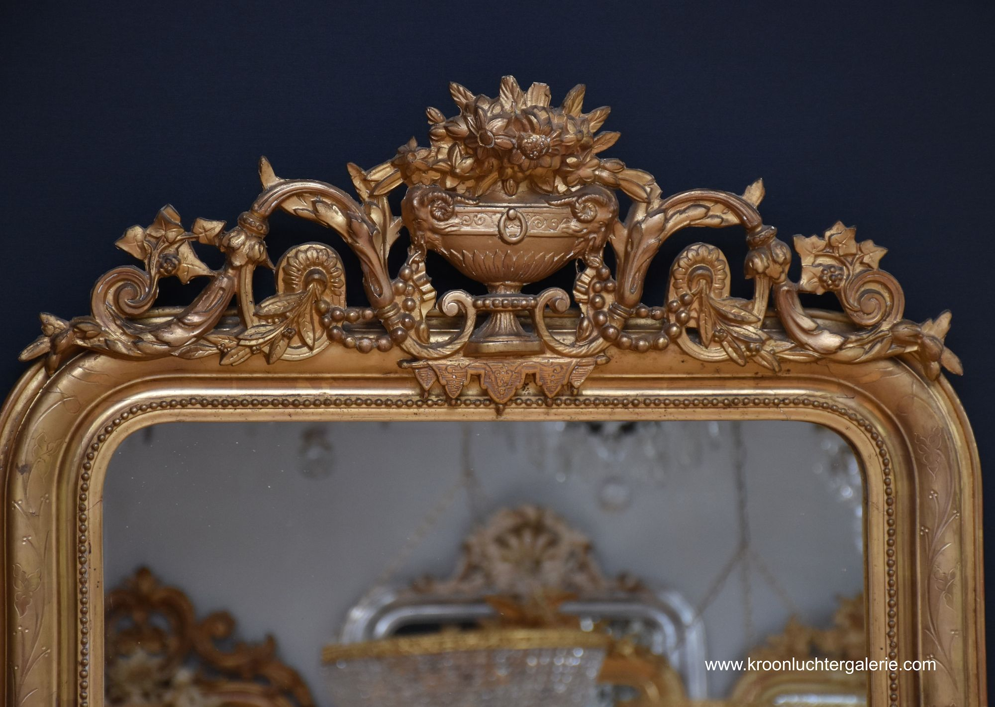 Antique French mirror with a crest, gold-leaf