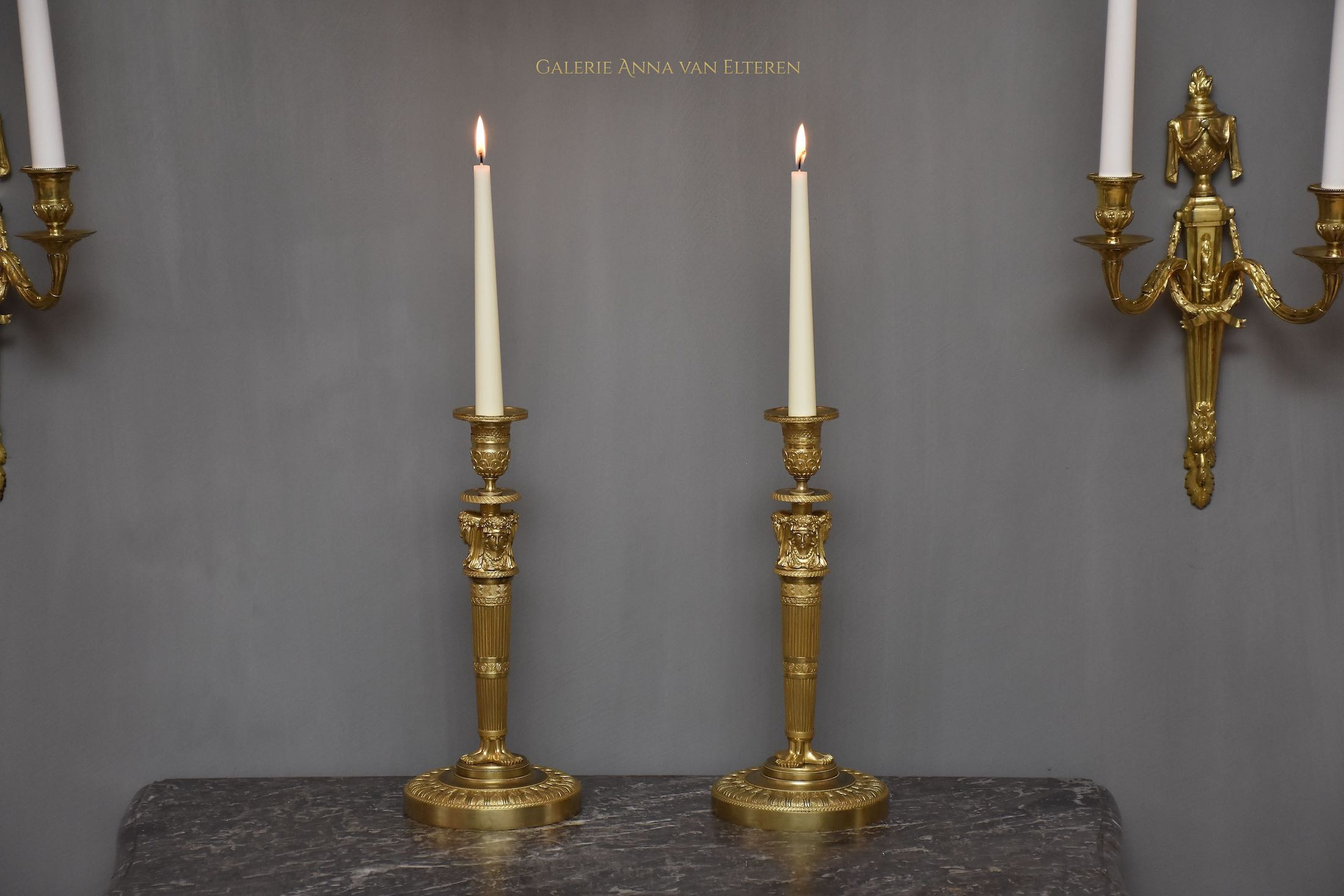 A pair of French Empire ormolu candlesticks